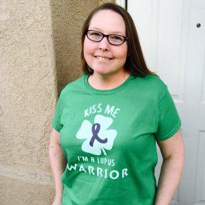 "Jennifer wearing a green shirt that says ""Kiss me, I'm a lupus warrior."""