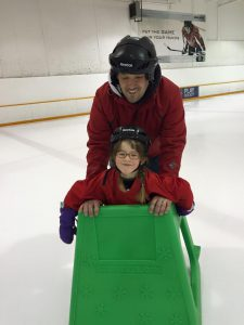 Gerry and his daughter ice skating, with Gerry behind her as she holds onto a green skating frame.