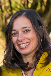 Photo of Isabel, smiling wearing a yellow jacket and fall colours in background.