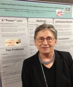 Annette stands in front of a poster presentation on patient-centric healthcare.
