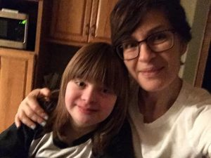 Brenda, with short dark brown hair and glasses, sits to the right with her arm wrapped around her daughter Holli, 12, who has Down Syndrome as they smile at the camera.