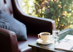 Black chair with pillow on it, table in front with cup of coffee and glass of water.